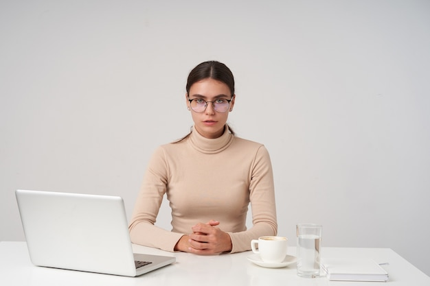 Serious young dark haired businesswoman wearing eyewear and formal clothes while sitting at table with laptop, folding hands on countertop while posing over white wall