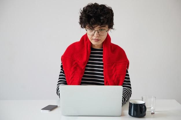 Серьезная молодая темноволосая кудрявая женщина с короткой модной стрижкой в очках во время работы на белом фоне с современным ноутбуком, глядя на экран с сосредоточенным лицом