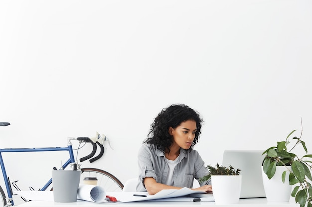 Serious young dark-skinned female designer sitting in front of open laptop computer