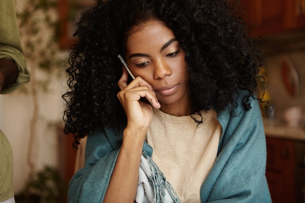 Serious young dark-skinned female with afro hairstyle having worried and unhappy look while talking on mobile phone