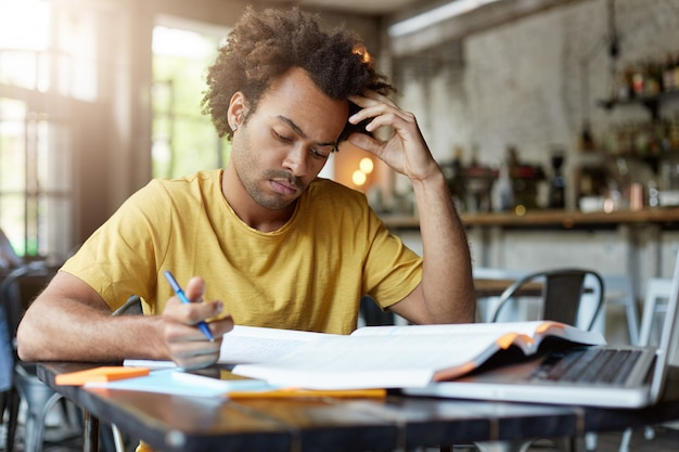 Серьезный молодой темнокожий мужчина с темными волосами и щетиной в желтой футболке, сосредоточенно глядя в блокнот, готовясь к экзамену или урокам, сидя в кафетерии, усердно работает