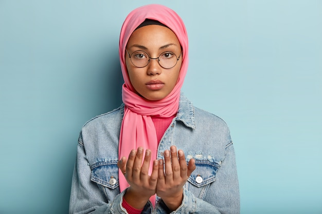 Serious young dark skinned woman looks at camera, prays indoor, keeps two hands in praying gesture