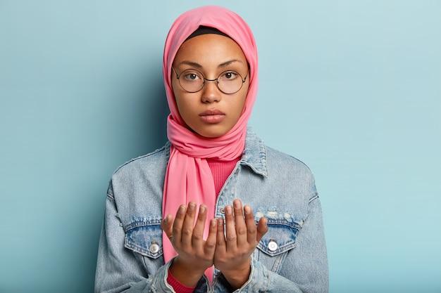 La giovane donna dalla pelle scura seria esamina la macchina fotografica, prega al coperto, tiene due mani nel gesto di preghiera