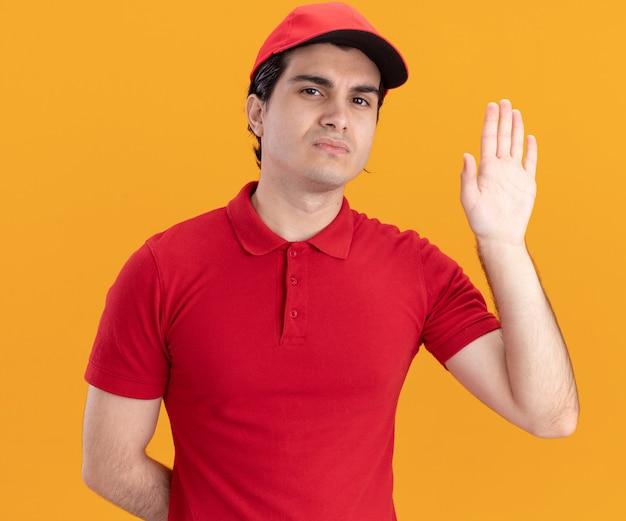 파란색 유니폼을 입고 모자를 쓴 진지한 젊은 배달원은 주황색 벽에 격리된 빈 손을 보여주는 앞을 바라보며 손을 뒤로 하고 있습니다.