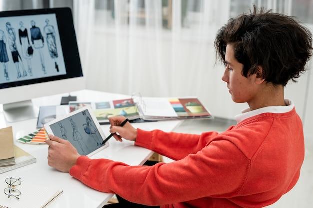 Серьезный молодой дизайнер с ручкой, указывающей на фотомодель на экране планшета, выбирая новые для сезонной коллекции