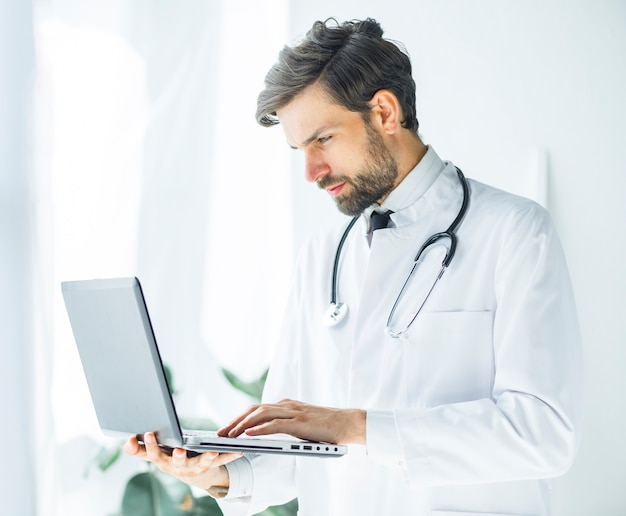 Serious young doctor browsing laptop