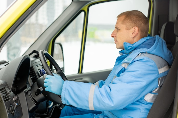 屋外で病気の人を救う救急隊員を待っている間、ステアのそばに座っている救急車の真面目な若いドライバー