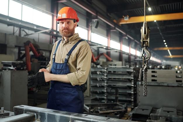 Серьезный молодой инженер в спецодежде и каске, стоящий рядом с огромной металлической деталью