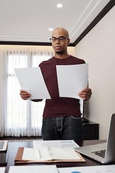 두 문서의 데이터를 재무 보고서와 비교하는 진지한 젊은 기업가