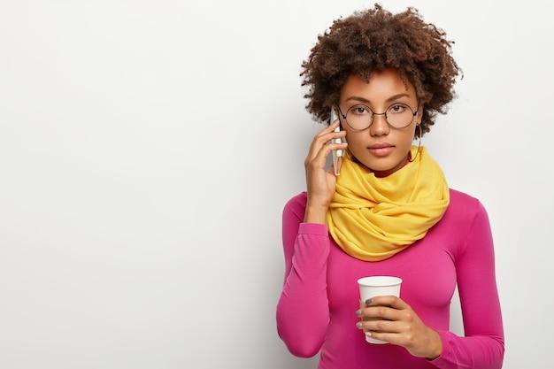 진지한 젊은 기업가가 시력 교정을 위해 안경을 쓰고 파트너와 공식 대화를 나눕니다.