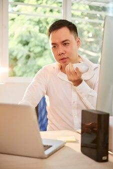 オフィスの机で働いて、同僚のために音声メッセージを録音する真面目な若い起業家