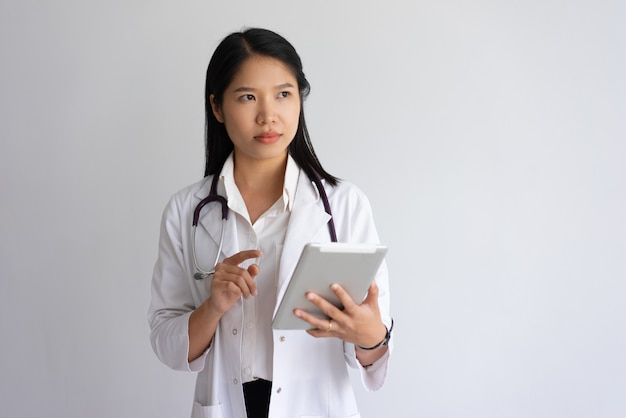 Serious young female doctor using tablet computer