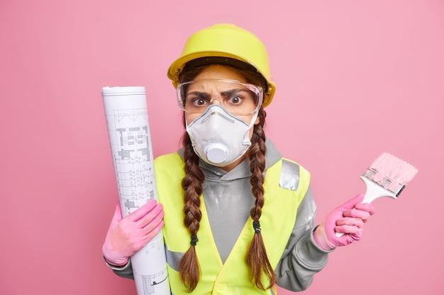 진지한 젊은 여성 엔지니어나 화가는 청사진과 브러시로 새 아파트에서 벽을 복원하고 페인트칠하느라 바쁘다