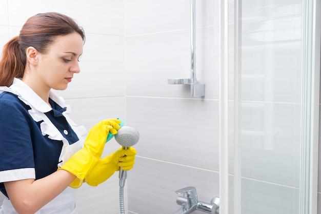 緑のスポンジで手持ちのシャワーヘッドの表面をこすり落とす深刻な若い女性の家政婦