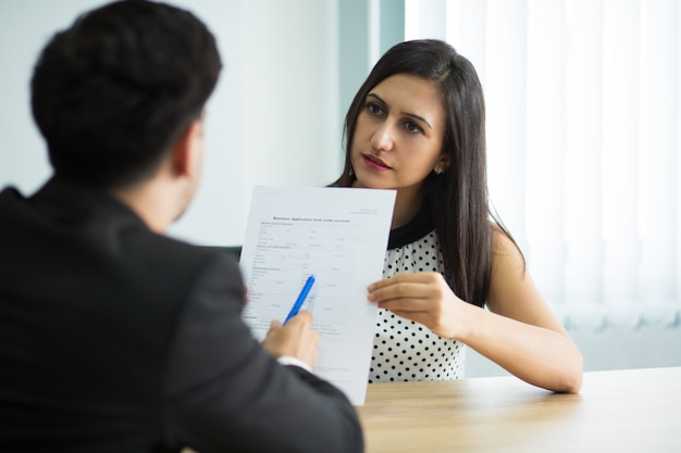 Serious young female manager showing contract to partner