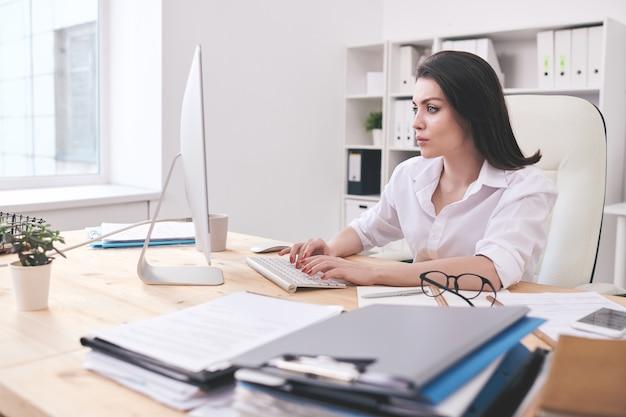 周りの書類の山と机でデータを入力しながらコンピューター画面を見ている真面目な若い女性のオフィスマネージャー