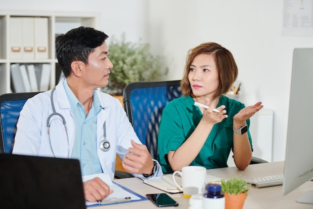 그녀의 환자의 일반 개업의에게 이야기하는 심각한 젊은 여성 외과 의사