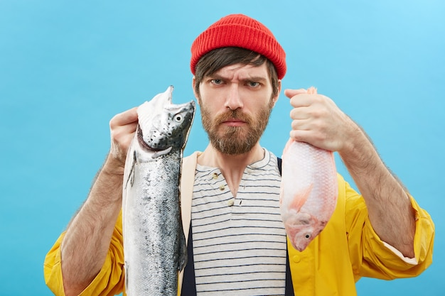 Serious young fisherman with beard holding two freshwater fish in both hands