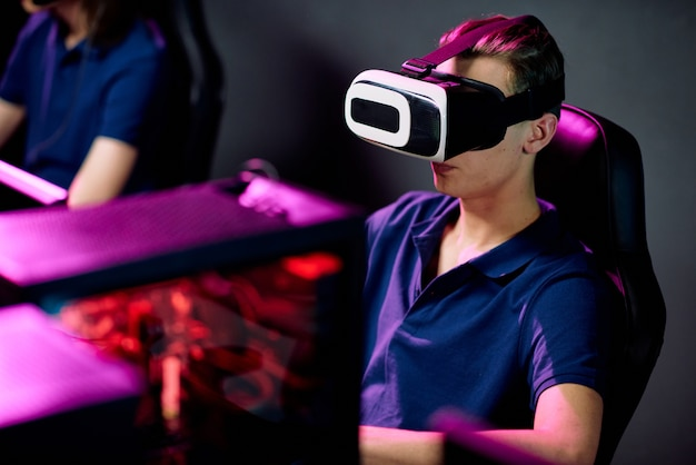 Serious young gamer in virtual reality headset playing videogame in modern cybersports club