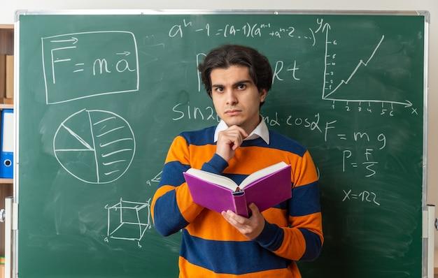 真面目な若い幾何学教師が教室の黒板の前に立って本を持って正面を見てあごに手を置いている