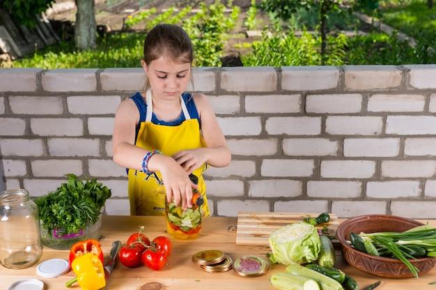 자급자족 개념의 대형 야외 테이블에서 일하는 유리병에 다양한 농장 신선한 야채를 병에 담는 진지한 어린 소녀