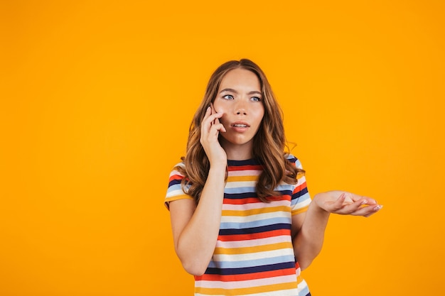 Серьезная молодая девушка позирует над желтой стеной, разговаривает по телефону.