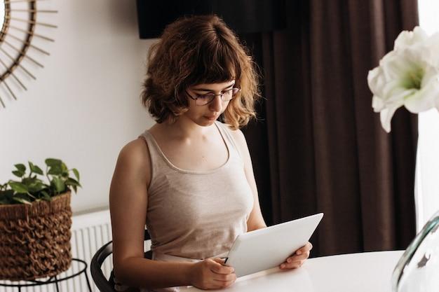 Серьезная молодая девушка учится онлайн. домашнее образование и домашнее обучение. онлайн-уроки на цифровом планшете