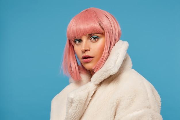 Серьезная молодая зеленоглазая красотка с модной розовой стрижкой, с цветным макияжем на лице, внимательно смотрит