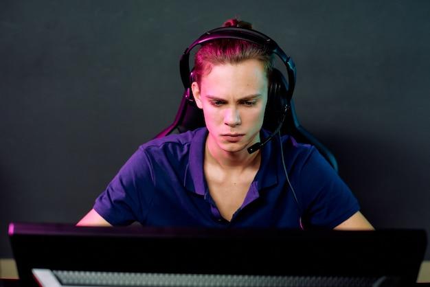 Серьезный молодой парень в наушниках с микрофоном сидит перед компьютером и играет в онлайн-игру