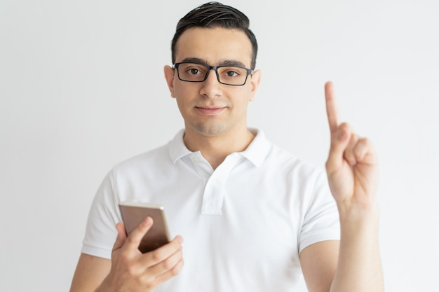 Serious young guy pointing upwards and holding smartphone