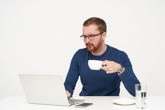 真面目な若いハンサムなひげを生やした男は、白い背景で隔離の集中した顔で彼のラップトップの画面を見ながら、上げられた手でお茶を持っています