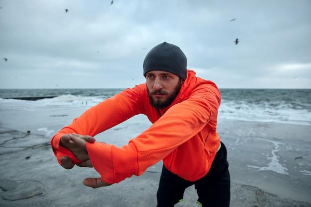 真面目な若いハンサムなブルネットのひげを生やした男性は、朝のトレーニングの前に、唇を折りたたんで背中の筋肉を伸ばし、嵐の灰色の日に海辺に立っています