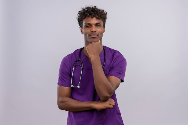 A serious young handsome dark-skinned doctor with curly hair wearing violet uniform with stethoscope keeping hand on chin