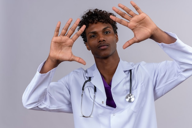 A serious young handsome dark-skinned doctor with curly hair wearing white coat with stethoscope showing number ten with hands
