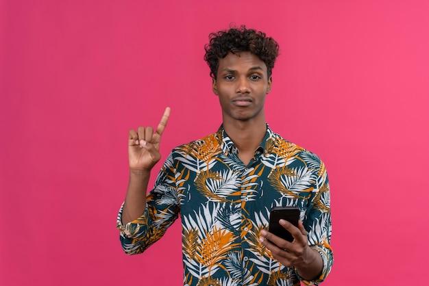 ピンクの背景に携帯電話を押しながら人差し指で1つのジェスチャーを作る葉プリントシャツに巻き毛を持つ深刻なハンサムな浅黒い肌の男