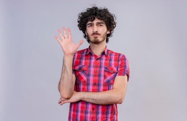 Un giovane uomo bello serio con capelli ricci in camicia controllata che mostra cinque dita che sollevano le mani
