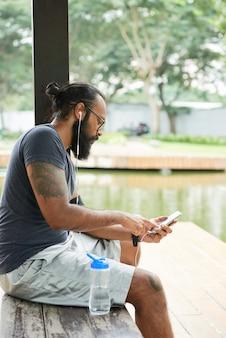 池のベンチに座って電話アプリを介して音楽を聴く入れ墨を持つ深刻な若いインドのひげを生やしたスポーツマン