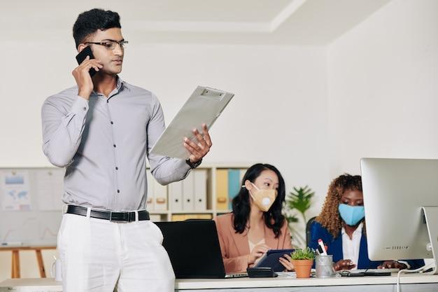 동료와 전화 통화를 할 때 문서의 세부 정보를 확인하는 심각한 젊은 인도 사업가