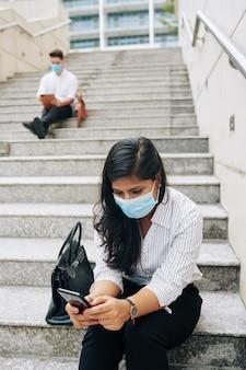 階段に座ってスマートフォンの画面でテキストメッセージを読んで医療マスクの深刻な若いインドの実業家