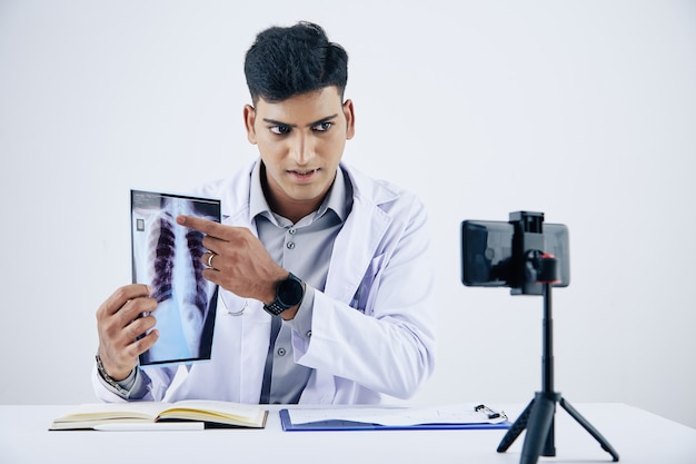 Serious young indian doctor sitting at desk, pointing at chest x-ray when giving consultation to patient