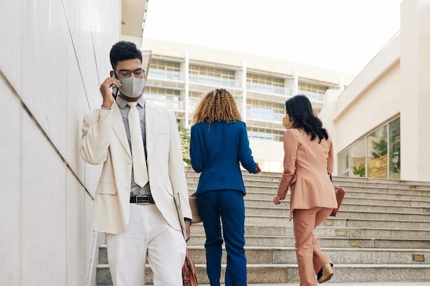 Серьезный молодой индийский предприниматель в защитной маске спускается по лестнице и разговаривает по телефону с коллегой или членом семьи
