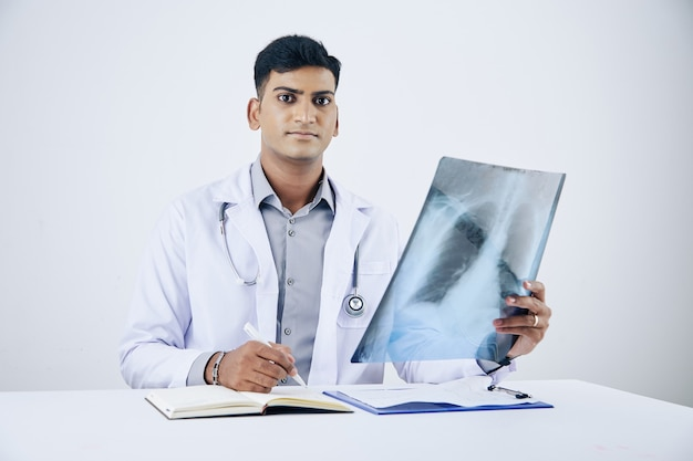 Serious young indian general practitioner analyzing chest x-ray and taking notes in medical history of client