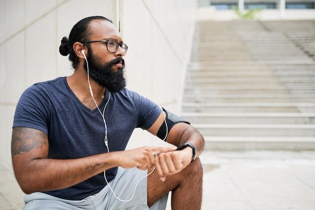 이어폰으로 오디오를 듣고 조깅 후 피트니스 시계로 맥박을 세는 수염을 가진 진지한 인도 청년