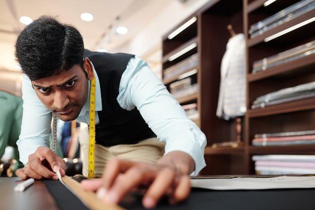 オーダーメイドのスーツに取り組んでいるときに黒いウール生地に直線を描く深刻な若いインドの仕立て屋