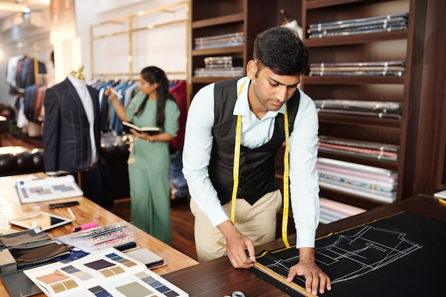 심각한 젊은 인도 재단사 분필로 어두운 직물에 재킷의 상단 전면 세부 사항을 그리기, 관리자는 백그라운드에서 마네킹에 맞춤형 sut를 확인