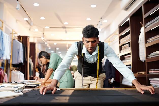 クライアントのためのオーダーメイドのスーツを作るために黒いウール生地を手入れする深刻な若いインドの仕立て屋