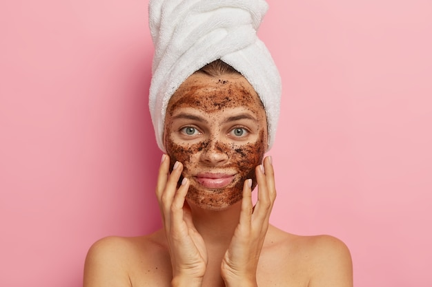 Serious young lady applies coffee scrub on face, does peeling of skin, removes pores, touches cheeks with hands, has naked body