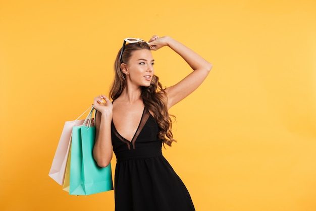 Serious young lady in black dress holding shopping bags.