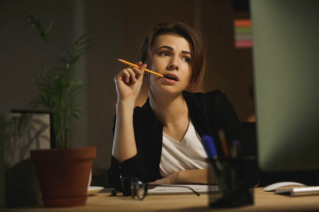 Serious young lady designer sitting in office at night
