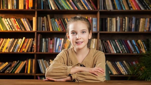 갈색 드레스를 입은 진지한 젊은 여성은 똑바로 보이고 도서관 책장에 기대어 나무 테이블에 앉아 있는 카메라를 향해 밝게 웃는다